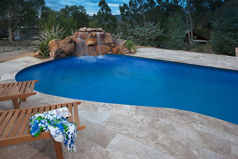 Swan view Concrete Freeform Pool with Rock Water Feature and Deck Chairs