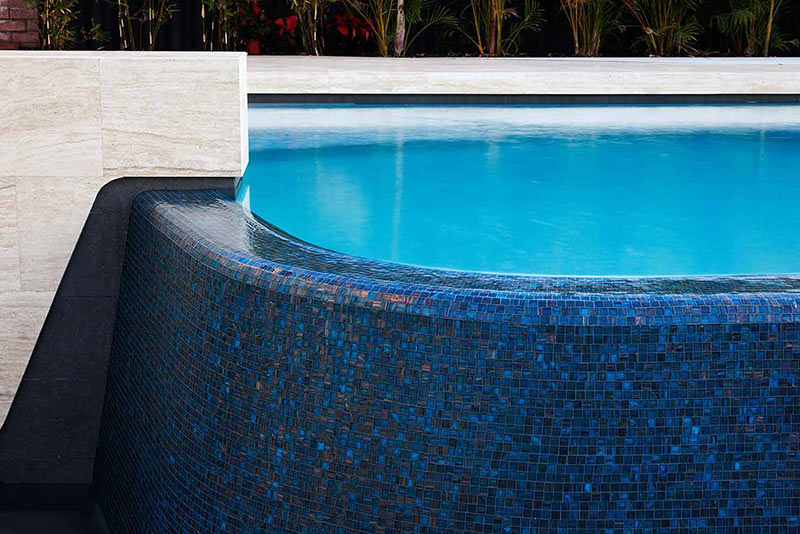 City Beach Concrete Geometric Pool with Fully Mosaiced infinity edge spillover