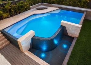 City Beach Concrete Geometric Pool with Freeform Benching and Infinity Edge
